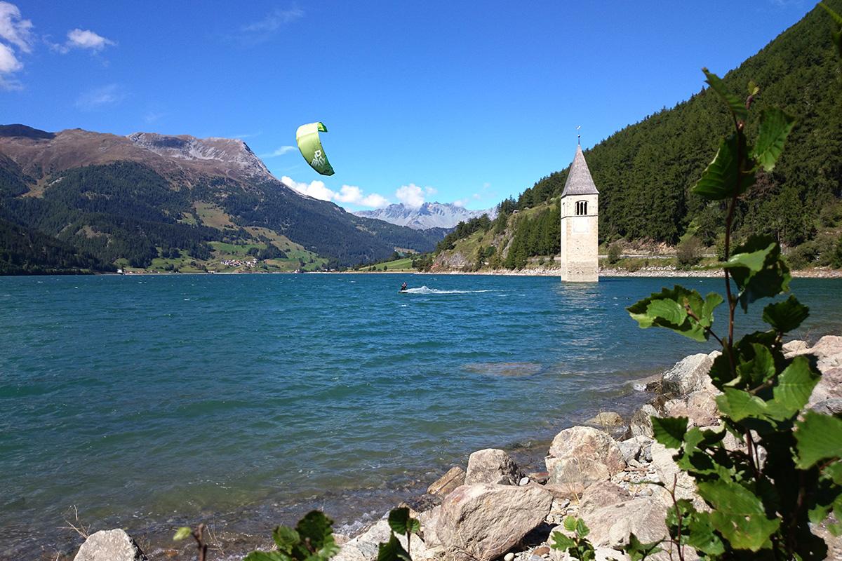 Kitesurfen auf dem Reschensee: Der Stausee bietet von Mai bis Oktober optimale Verhältnisse – auch für Anfänger. Auf den umliegenden Wiesen wird mit dem Kite geübt, bevor es ins Wasser geht. Hingucker ist der aus dem Wasser ragende Kirchturm des ehemaligen Dorfes.