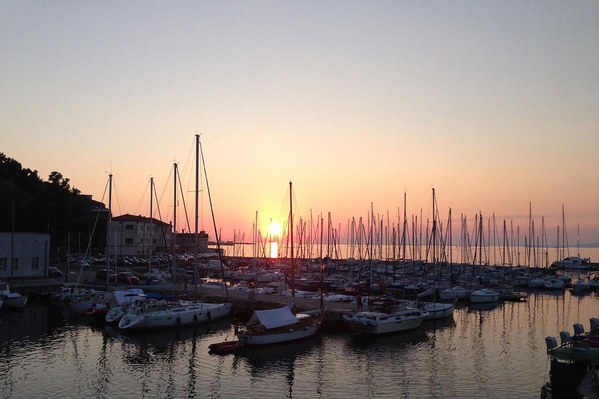 Alpe-Adria-Trail. Sonnenuntergang am Hafen von Muggia