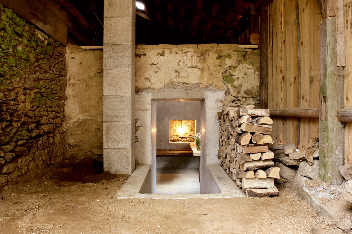 Peter Haimerl Architekt. Die schlichte Bauweise der alten Bayerwaldhäuser hat Haimerl versucht zu erhalten. Der Durchgang führt zur Küche in einem der Betonkuben