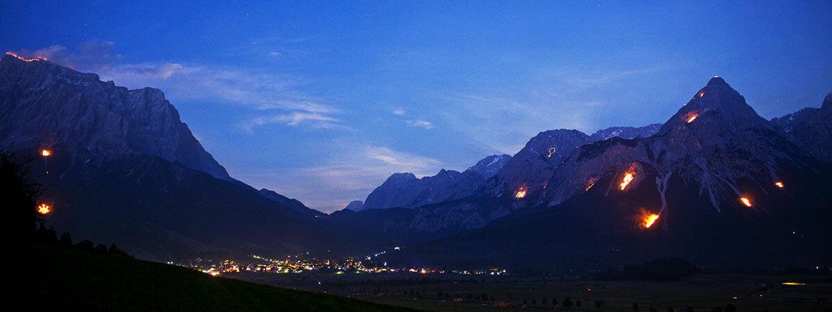 Berge in Flammen – Herz-Jesu-Feuer. Am 24. Juni 2017 verzaubern Feuermotive die Berge der Tiroler Zugspitz Arena bei den traditionellen Sonnwendfeuern