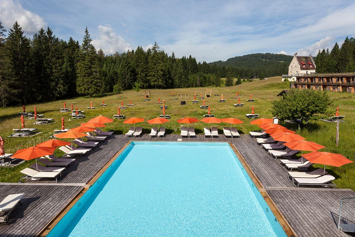 Das Kranzbach – Onsen-Premiere in Oberbayern. Direkt an seinen neuen Onsen grenzt die 130.000 Quadratmeter große Bergwiese, in die im Sommer kleine Inseln für einzeln stehende Liegen und Sonnenschirme gemäht werden