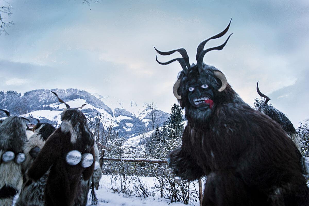 Die Dämonen-Vertreiber. Schaurig schön: Die geschnitzten Masken der Rauriser Toifi (o., Teufel) sind mit roter, weißer und schwarzer Farbe bemalt. Aus dem Maul hängt den Toifin eine rote Stoffzunge. Auf den traditionellen Holzmasken sind Ziegenbock- oder Widderhörner angebracht. In zotteligen Mänteln aus Schafsfell, mit einer Rute in der Hand und mit Schellen und Glocken ziehen sie durch das Tal. Momente vor dem Umzug: Im Morgengrauen kleiden sich die Passen in der Zimmerei Malzer in Bad Hofgastein ein (u.)