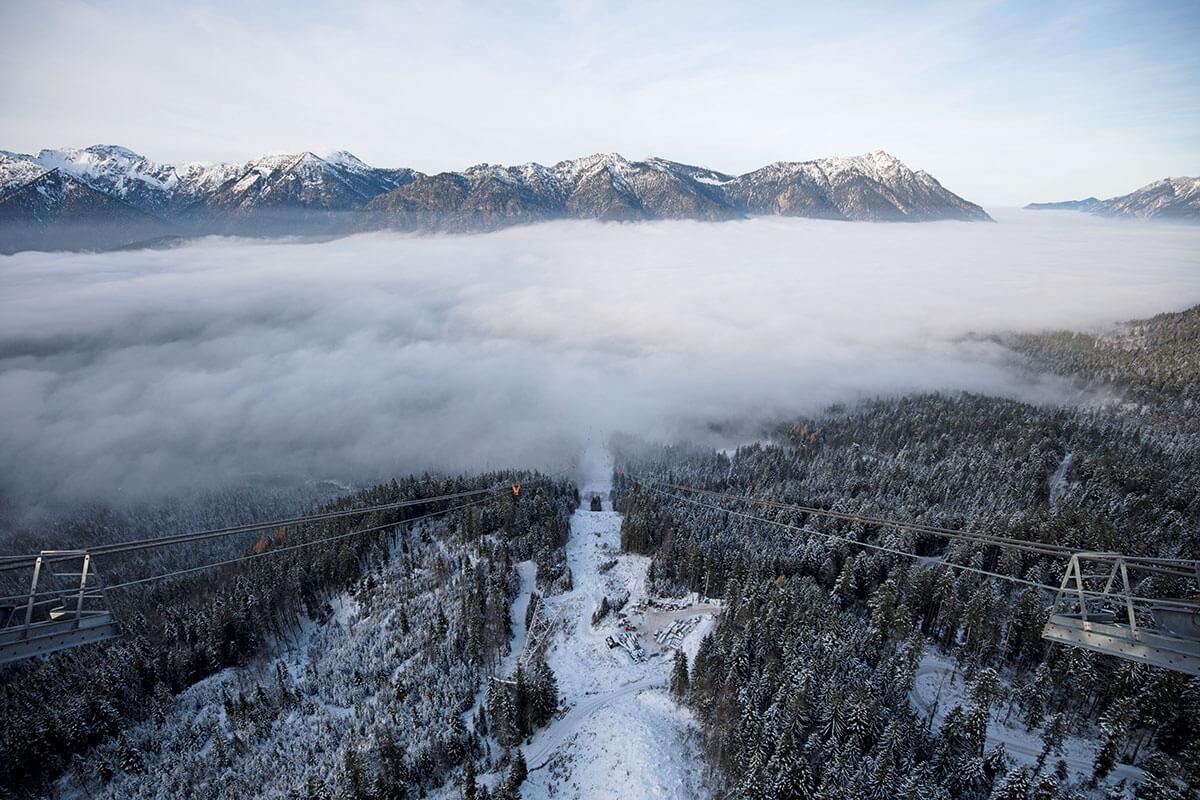 Seilbahn Zugspitze – Drahtseilakt. GANZ SCHÖN LUFTIG: Der Blick von der neuen Seilbahnstütze auf die Ammergauer Alpen. Unten liegt die bereits abgebaute Stütze der alten Bahn im frischen Neuschnee