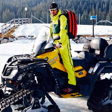 """Loipenrettung – """"Fehler macht nur, wer gar nichts tut"""". Früher mussten Verletzte durchschnittlich 45 Minuten auf Hilfe warten. Dank Martin Tauber und seinem 20köpfigen Team hat sich die Einsatzzeit halbiert. Mit seinem bis zu 45 kmh schnellen Schneemobil ist er oft vor dem alarmierten Hubschrauber vor Ort."""